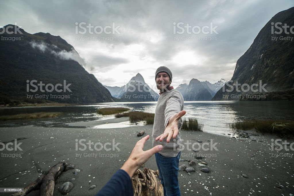Man offering helping hand to partner stock photo