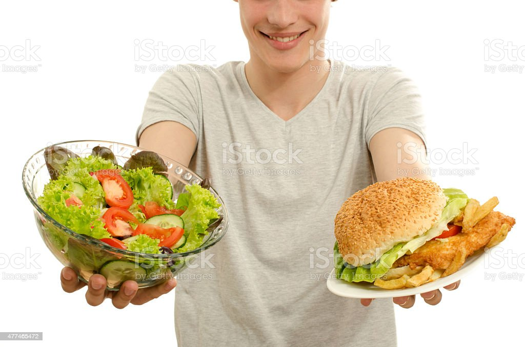 Man offering you a salad and a hamburger. stock photo