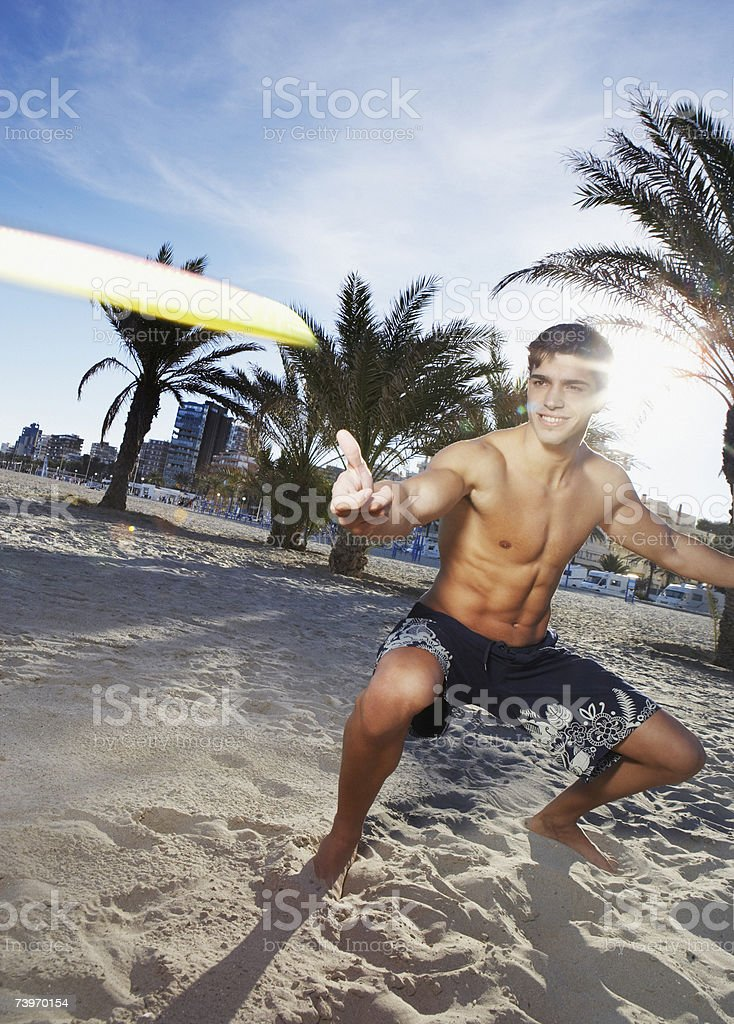 Man on a beach tossing a flying disc toy stock photo