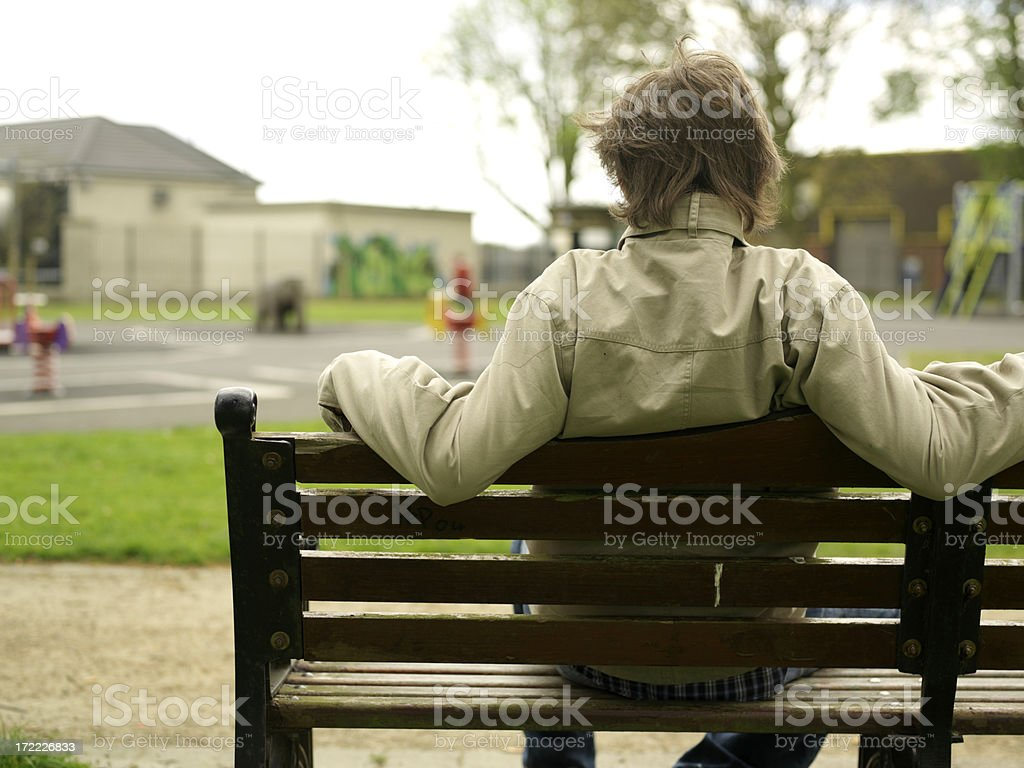 man on a bench at the park stock photo