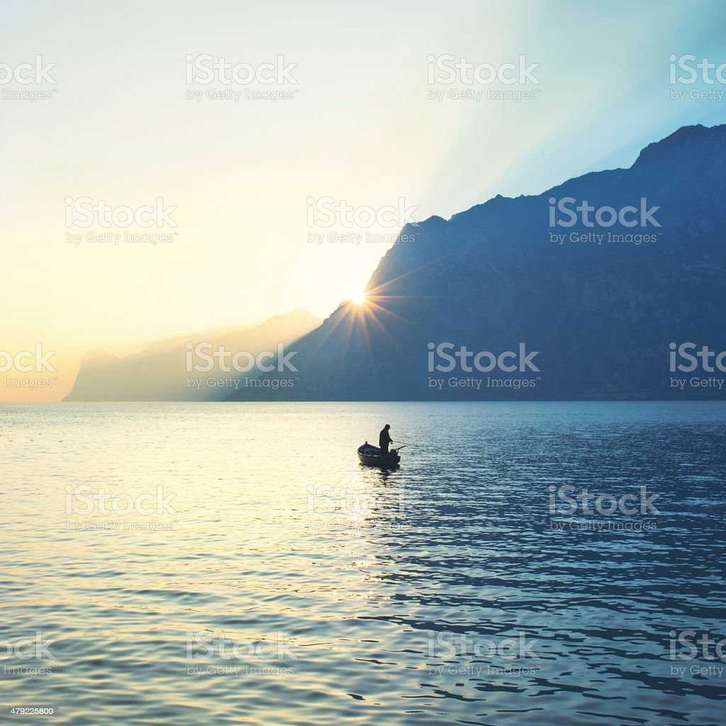 man on a canoe fishing under an amazing sunset stock photo