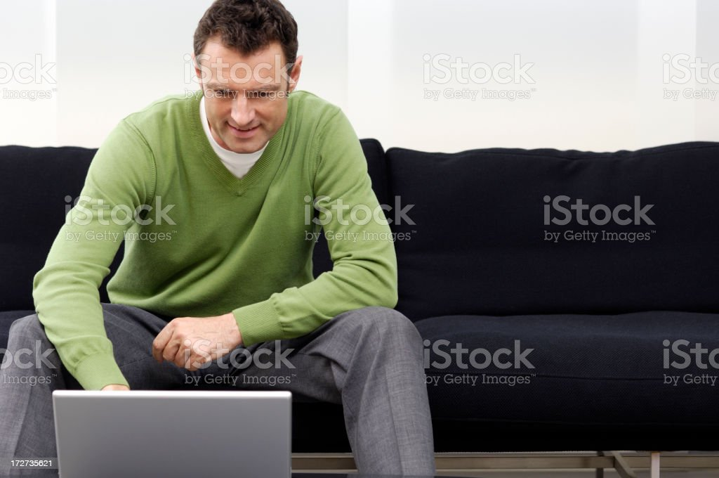 Man on a couch, browsing royalty-free stock photo