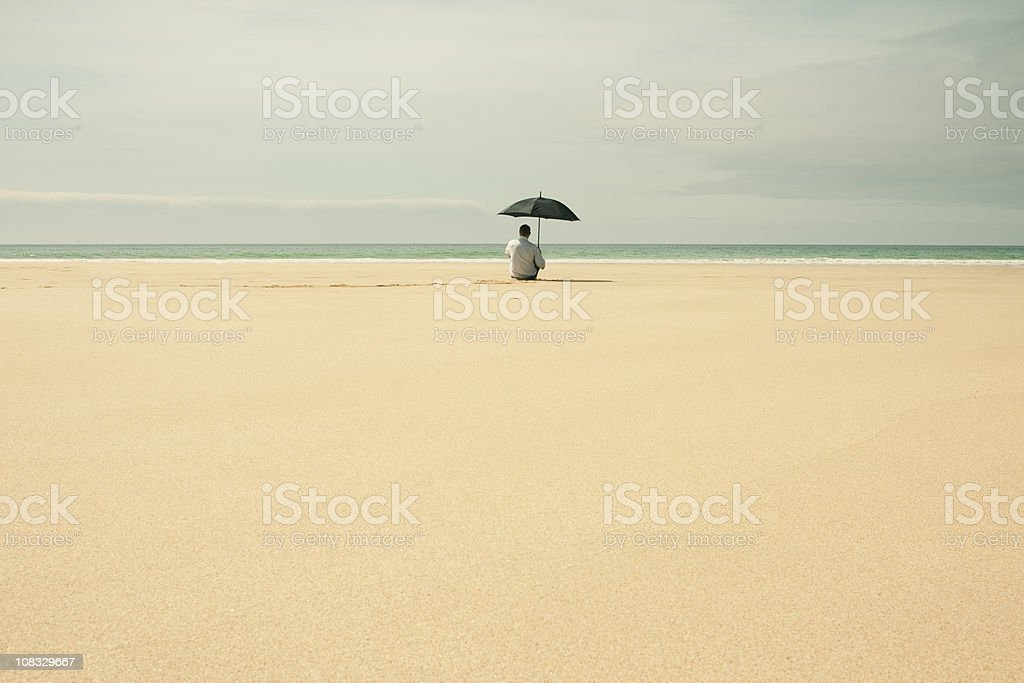 Man on a deserted beach sitting with umbrella royalty-free stock photo