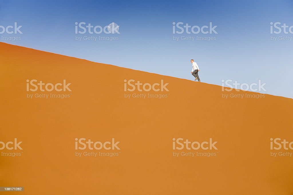 man on a dune climbing to the moon stock photo