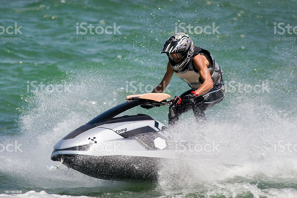 A man on a jet ski going through water with a helmet on royalty-free stock photo