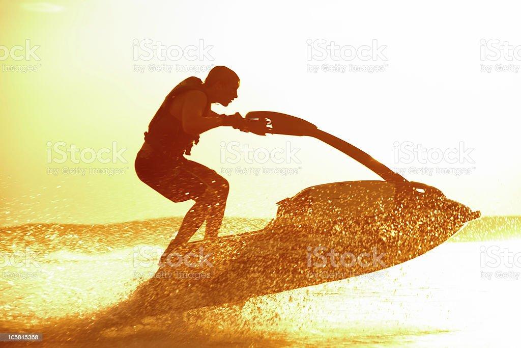 A man on a jet ski speeding through the waters stock photo