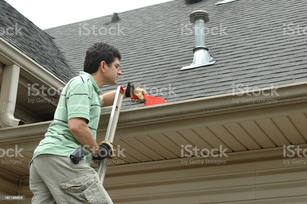 Man on a Ladder Cleaning Leaves from Gutter stock photo