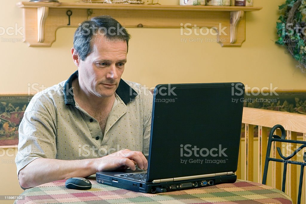 A man on a laptop working from home stock photo
