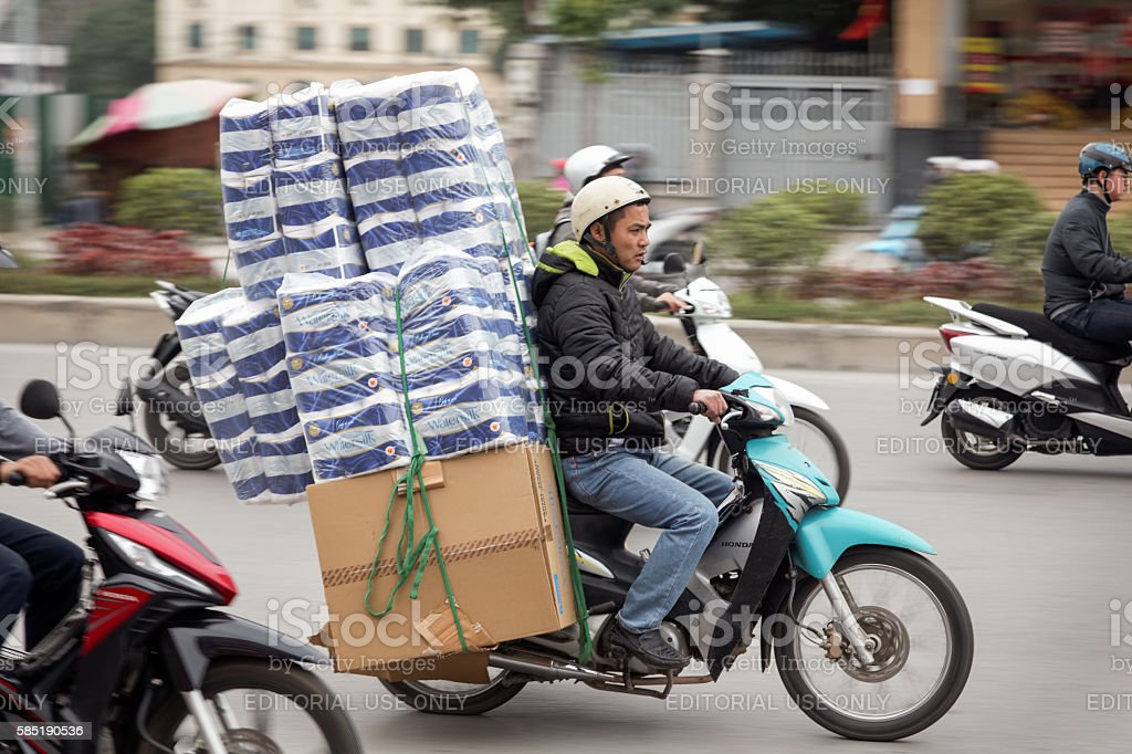 Man on a motorbike carrying toilet paper stock photo