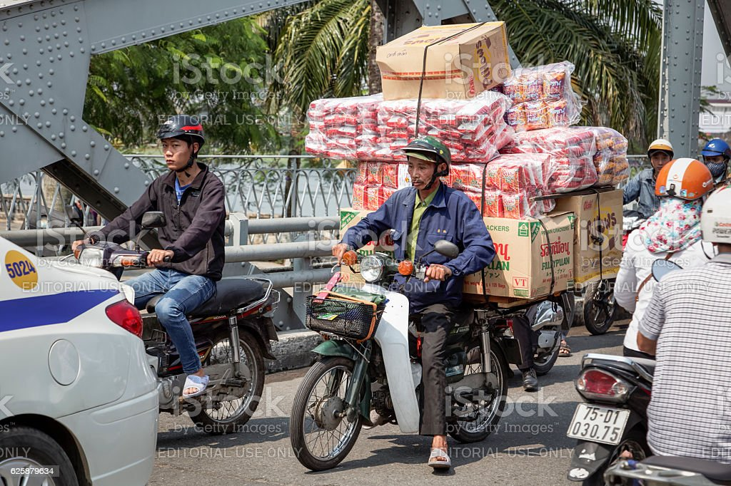 Man on a motorbike with a lot of boxes stock photo