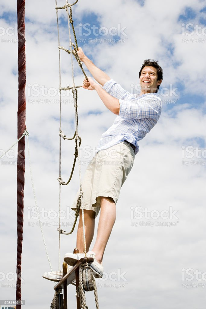 Man on a Sailboat Climbing a Rope Ladder stock photo