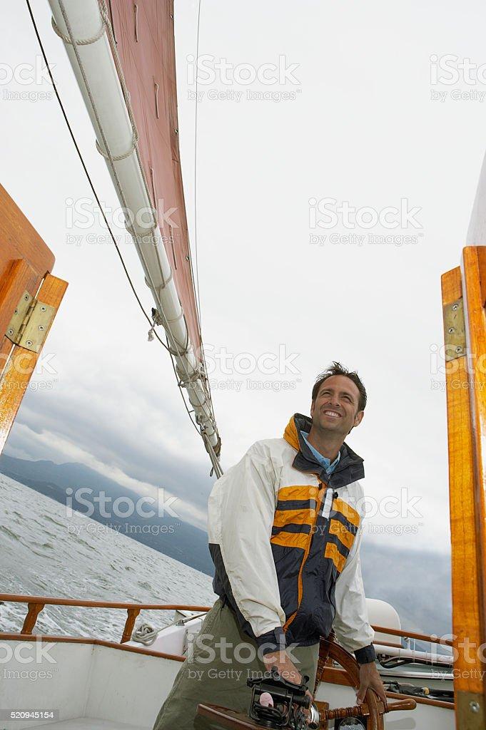 Man on a sailboat stock photo