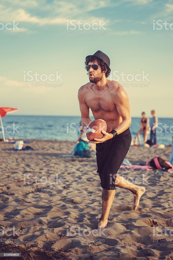 man on beach catching football stock photo
