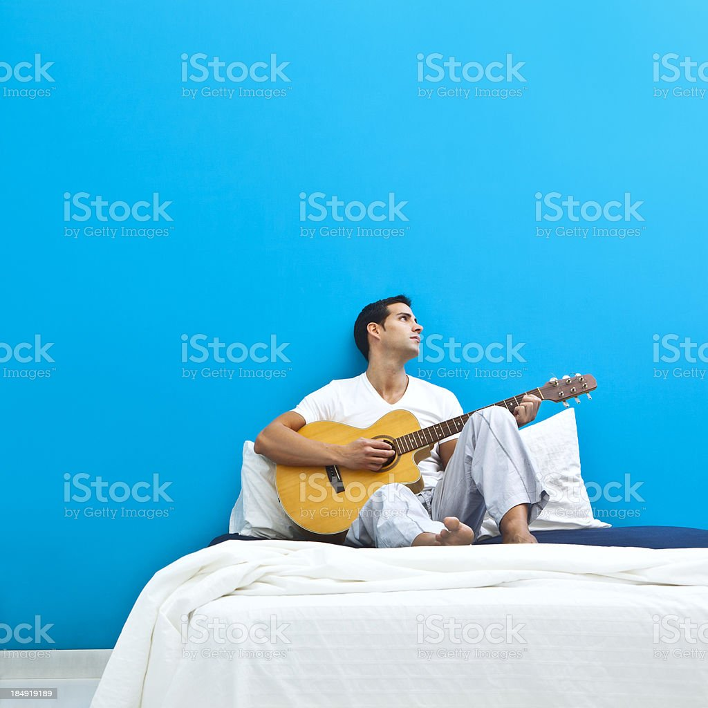 Man on bed playing guitar stock photo