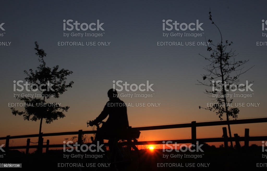 Man on bicycle at sunrise stock photo