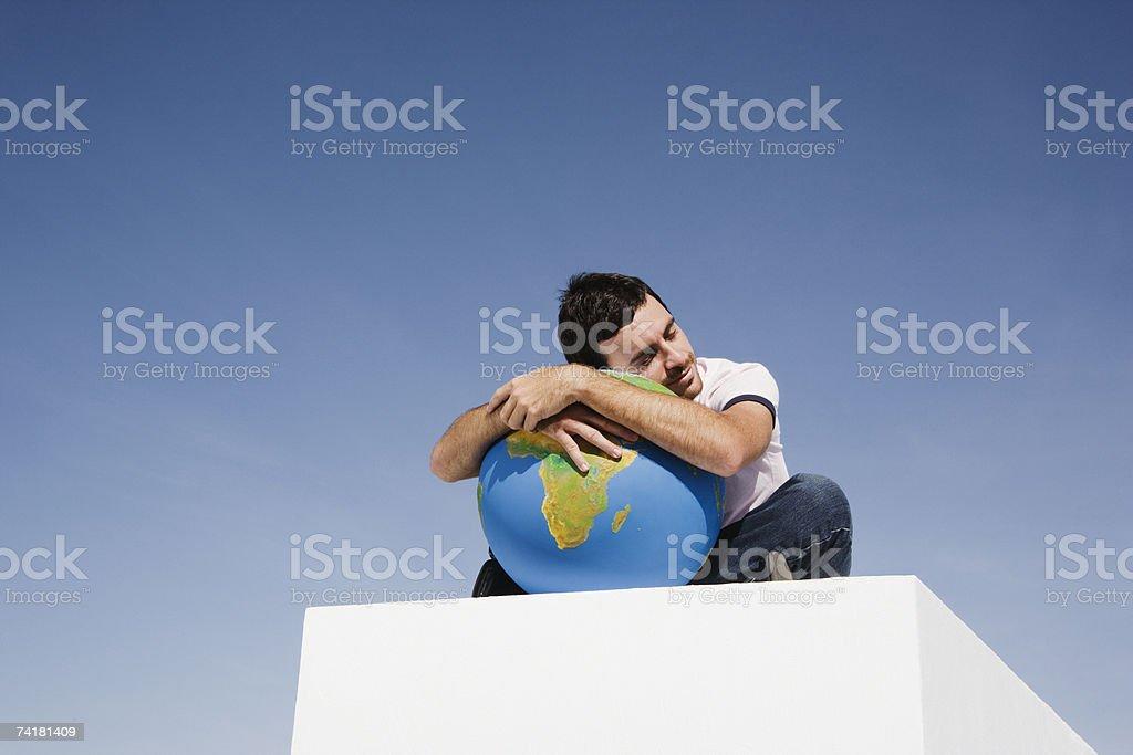 Man on block outdoors holding globe stock photo
