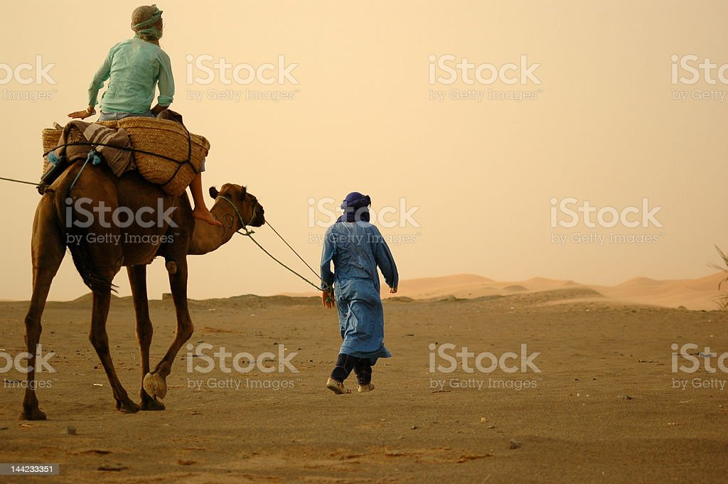 A man on camel back being lead across the desert royalty-free stock photo