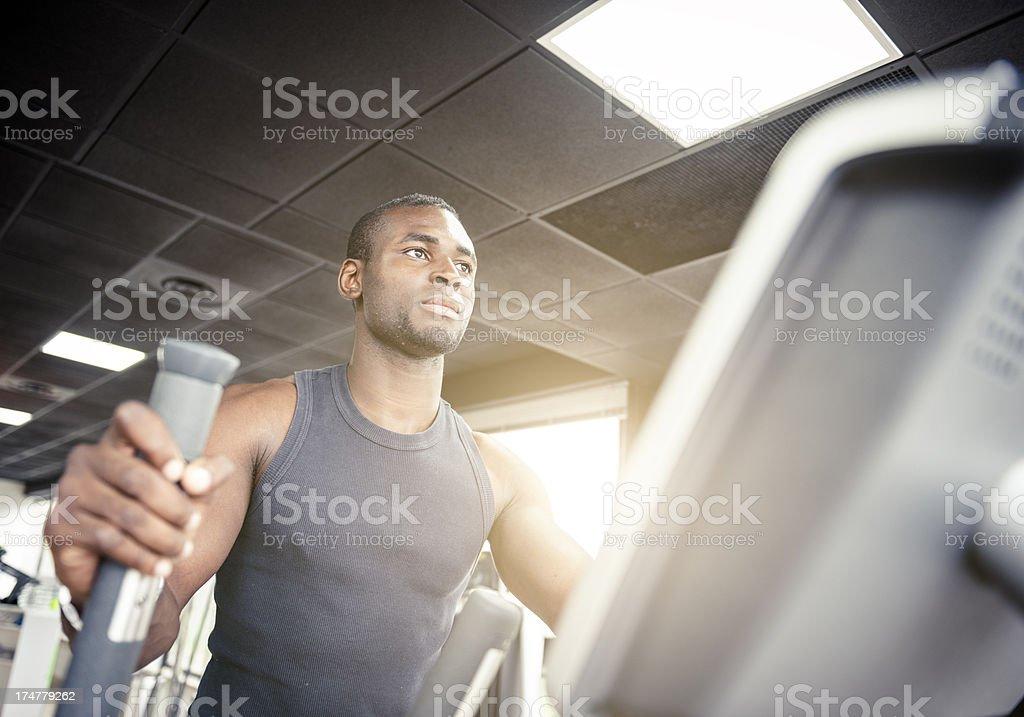 Man on Cardio machine inside a gym stock photo