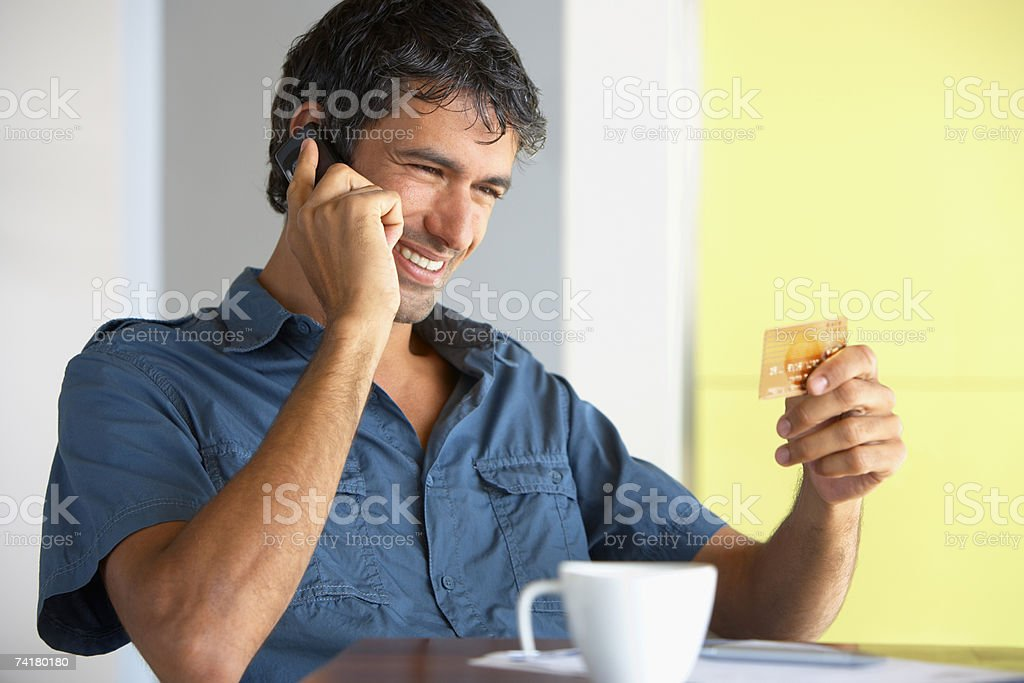 Man on cell phone with credit card and coffee cup royalty-free stock photo