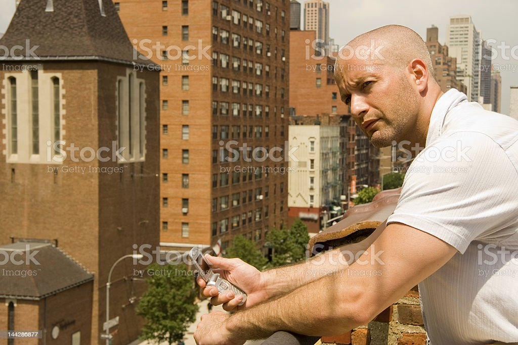Man on city roof holding cell phone royalty-free stock photo