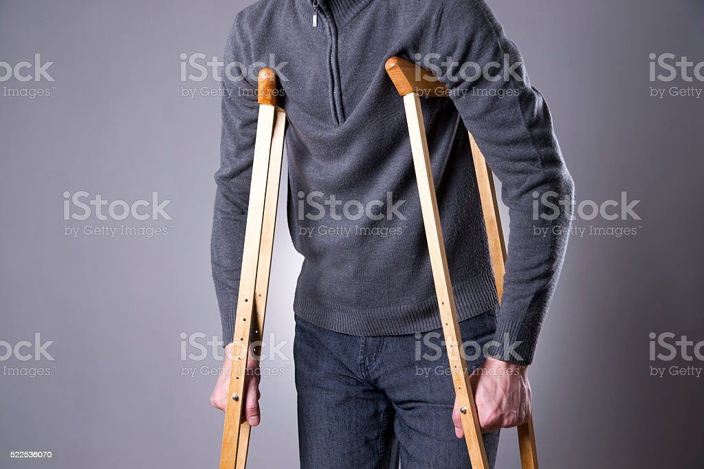 Man on crutches on a gray background stock photo