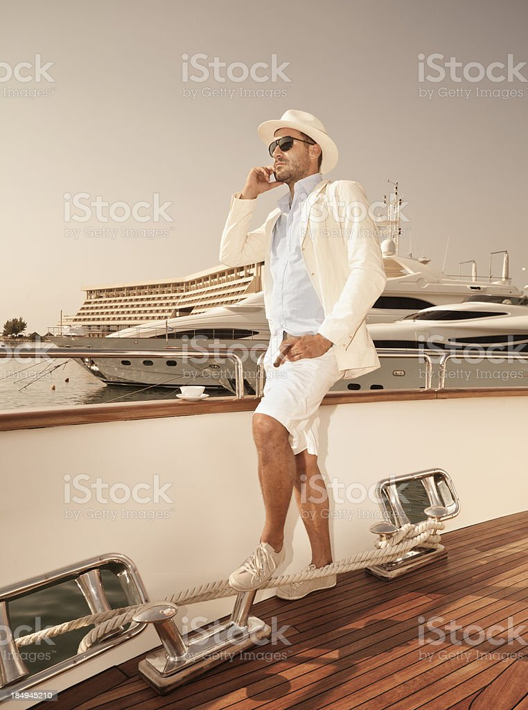 Man on deck of a boat with a yacht behind it stock photo