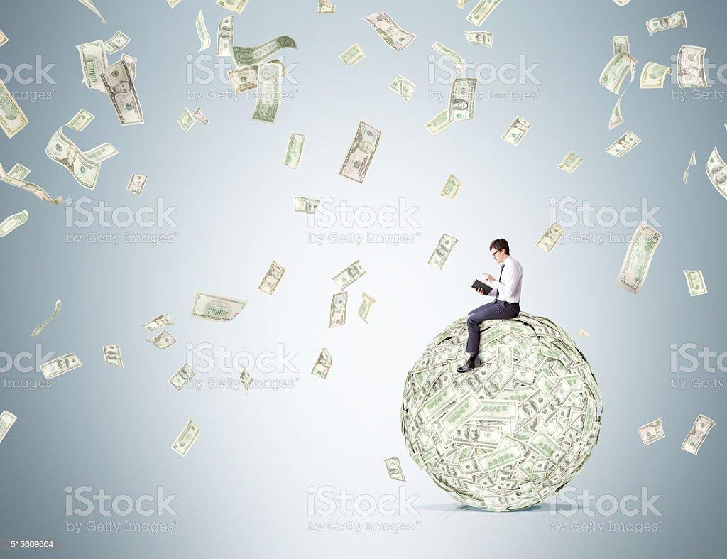 Man on dollar ball reading stock photo