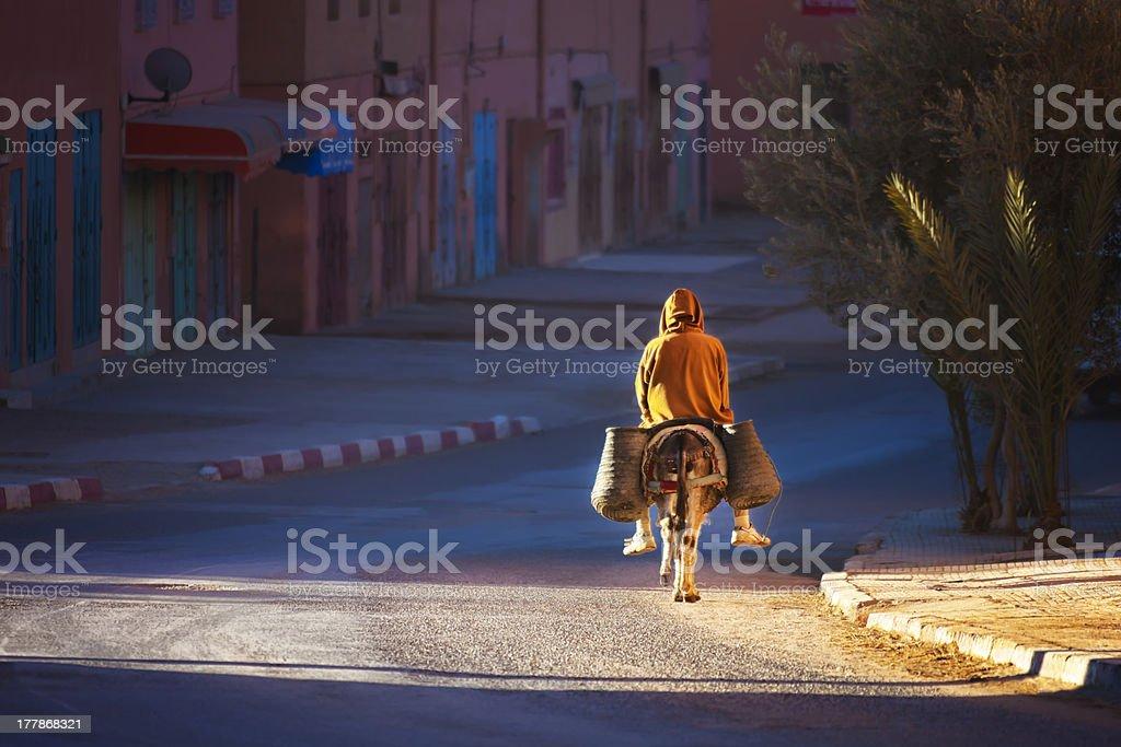 Man on donkey rides early morning. royalty-free stock photo