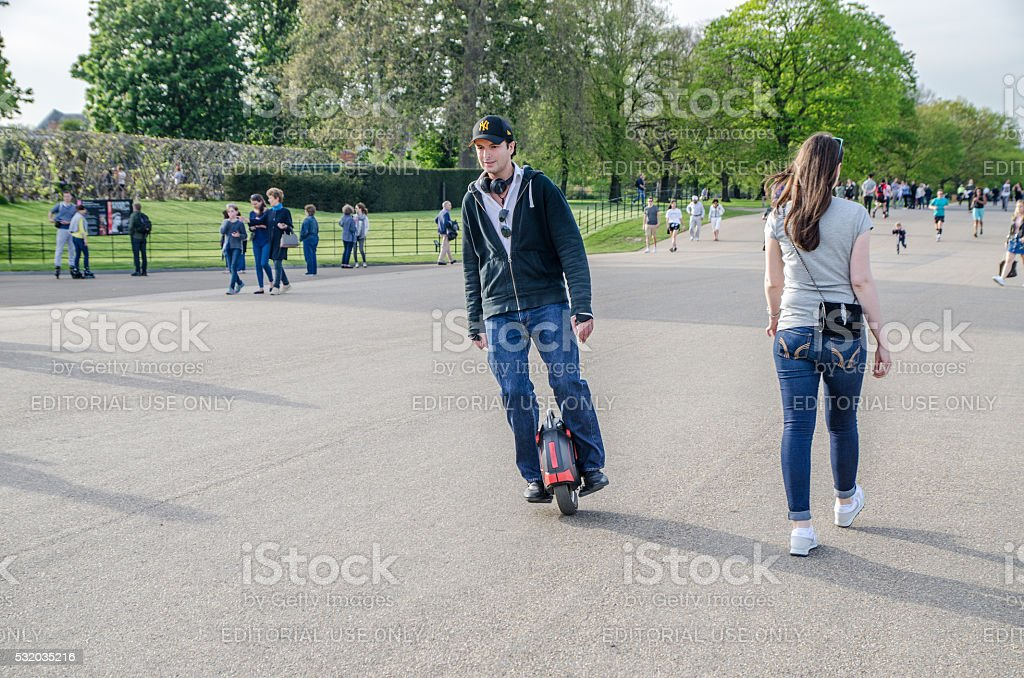 Man on electric unicycle passing by stock photo