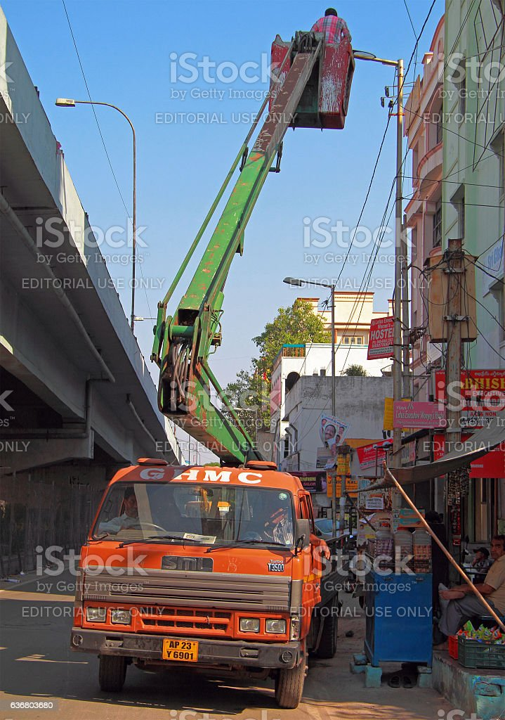 man on elevation deck of manipulator is mounting electric lamps stock photo