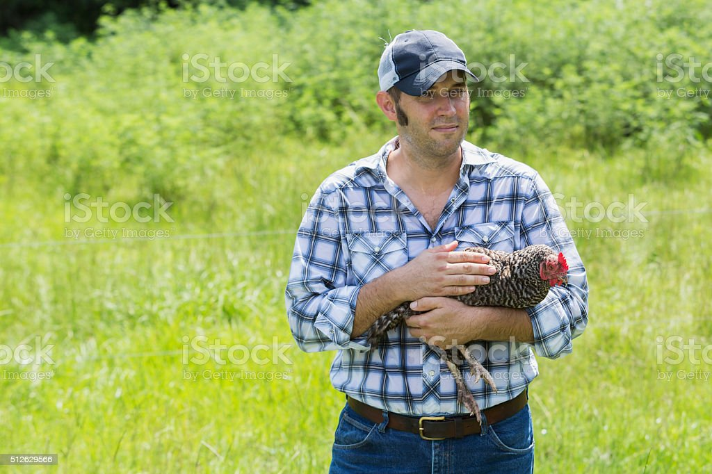 Man on farm holding chicken stock photo
