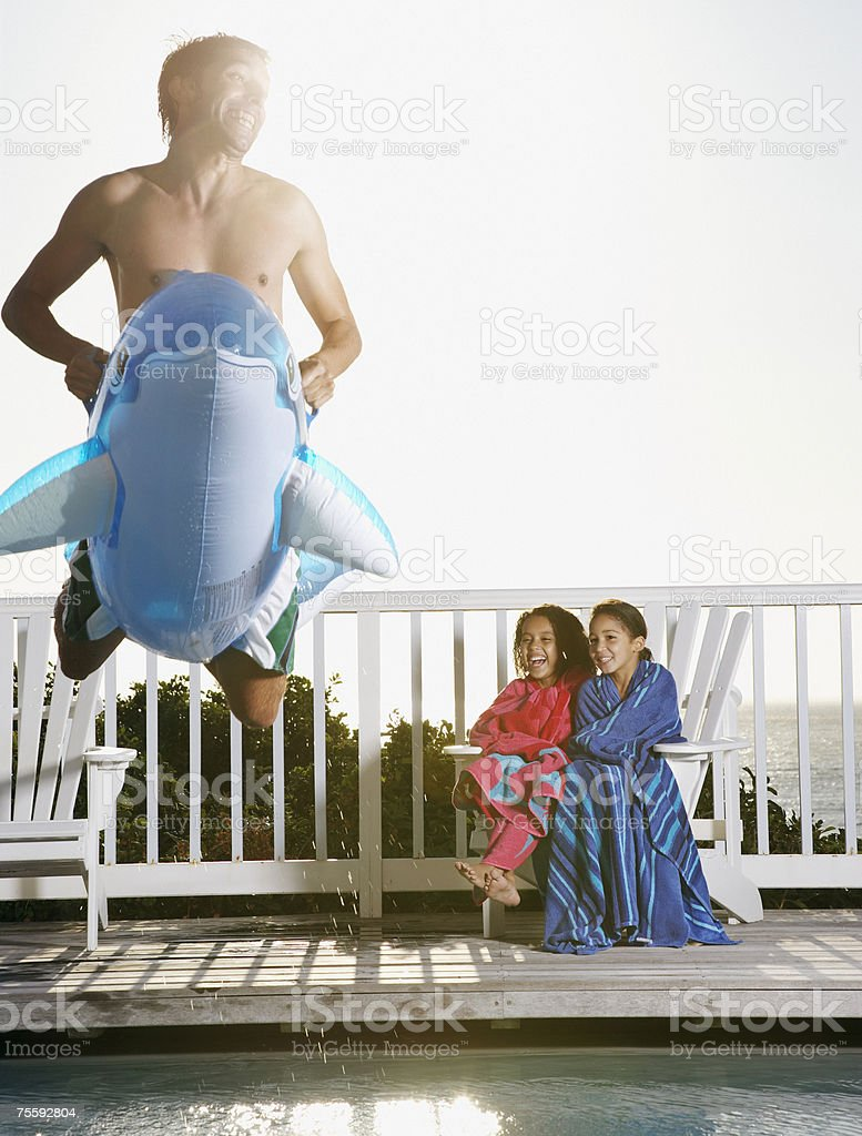 Man on flotation device leaping into pool with girls laughing royalty-free stock photo