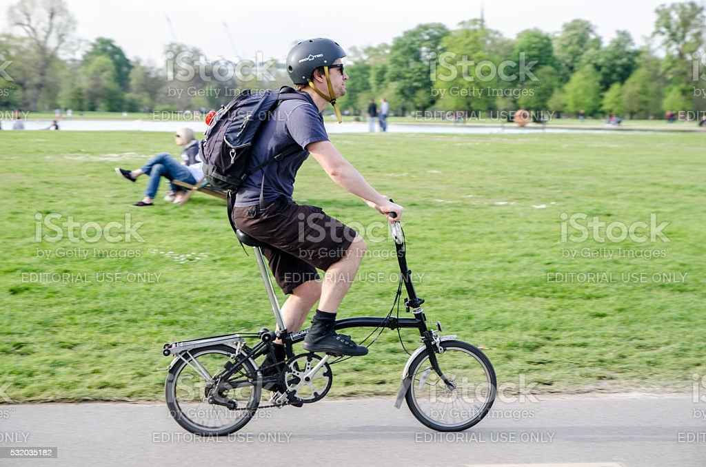 Man on foldable bicycle passing by stock photo