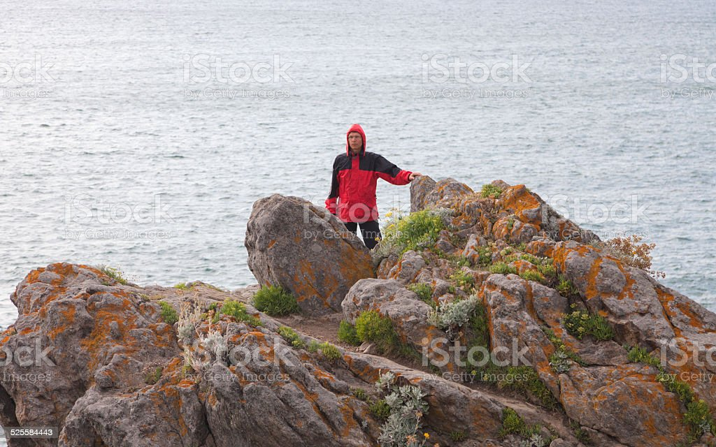 Man on granite cliffs in Brittany stock photo