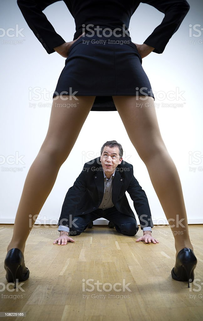 Man on Hands and Knees with Woman Standing Above Him stock photo