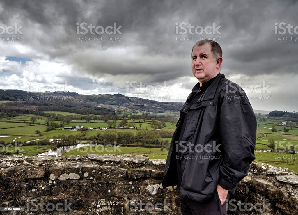 Man on hilltop with view of surrounding countryside stock photo