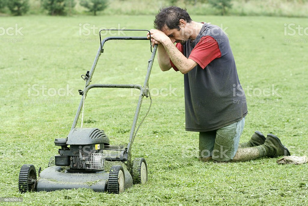 A man on his knees with his lawnmower stock photo