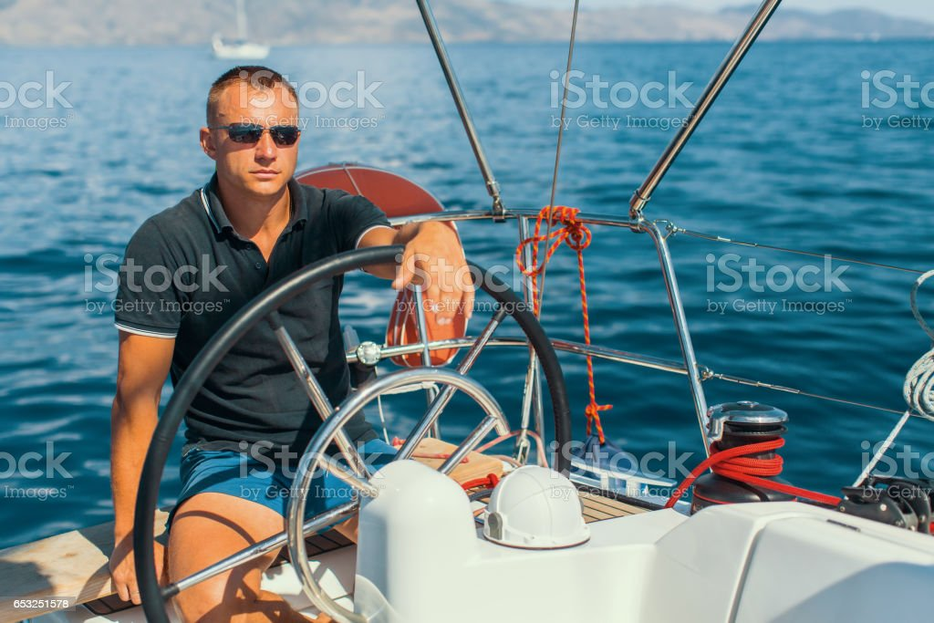 Man on his sailing yacht boat. stock photo