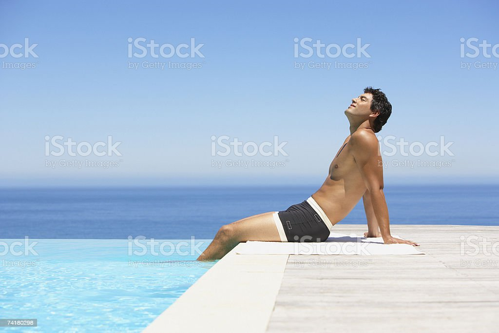 Man on infinity pool deck in swimsuit royalty-free stock photo