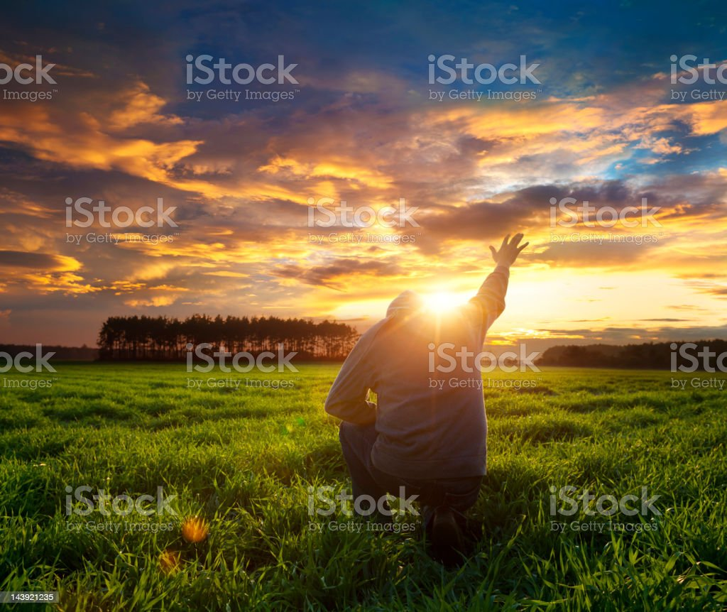 Man on meadow praying to god facing the sun stock photo