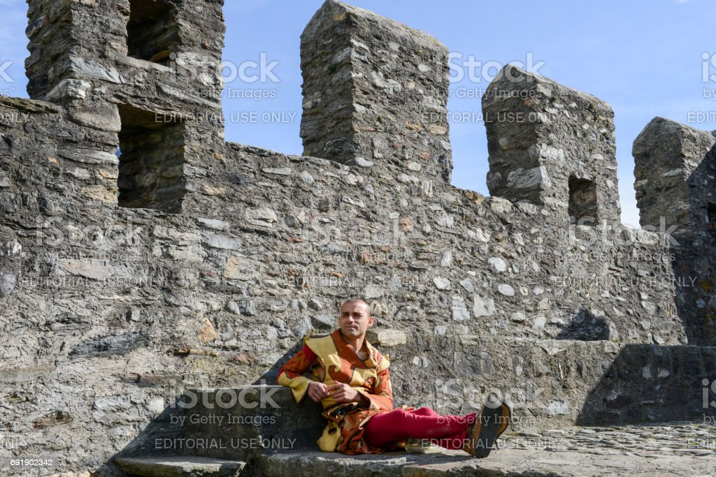 Man on medieval clothes sitting on the walls of Castelgrande stock photo