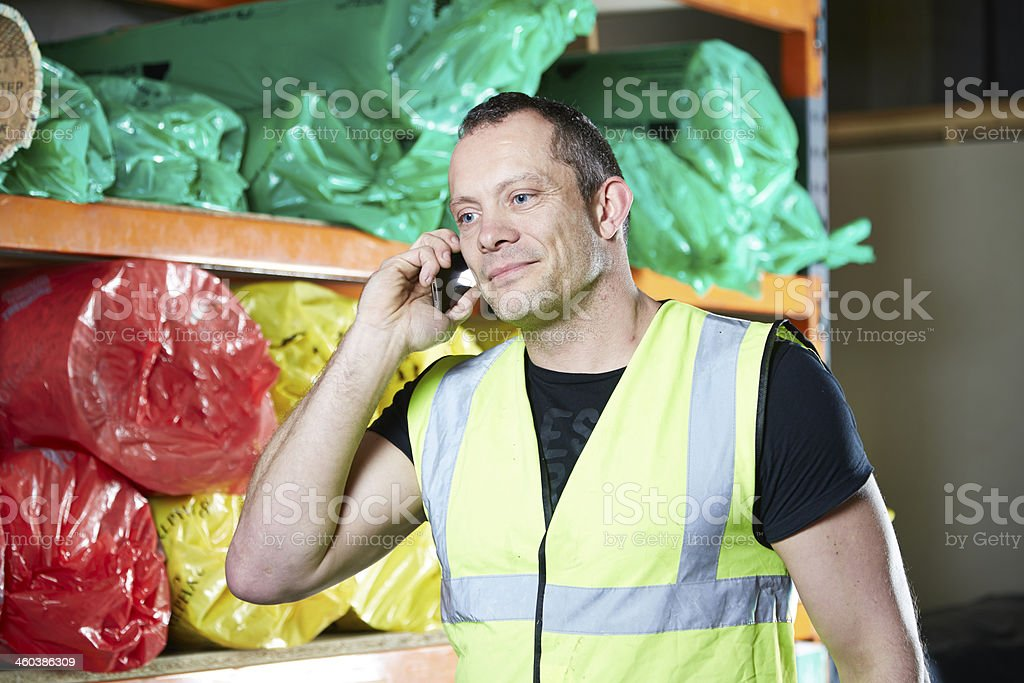 Man on mobile phone in warehouse stock photo