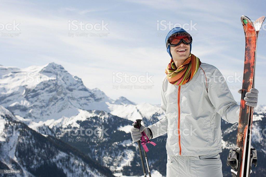 Man on mountain holding skis stock photo