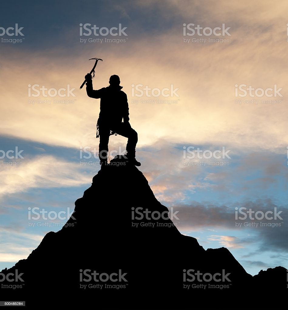 man on mountains with ice axe in hand stock photo