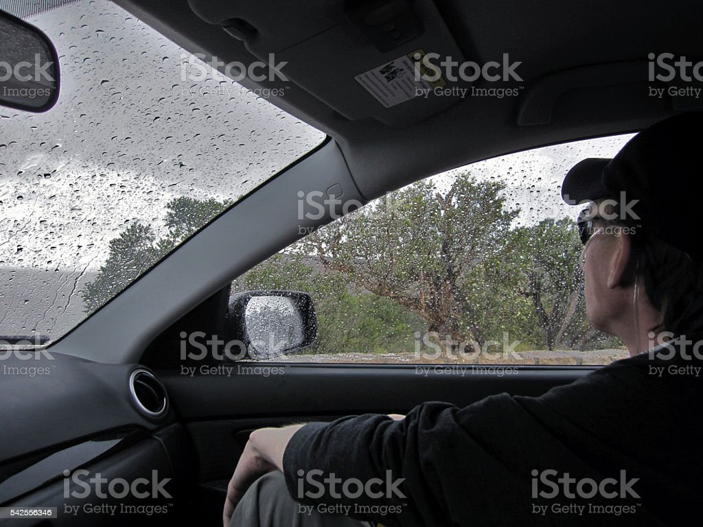 Man on Oxygen Inside of Car During Rainstorm stock photo