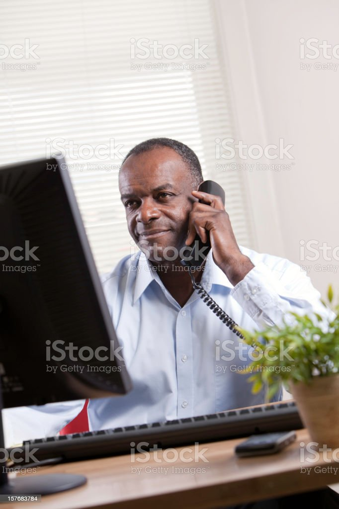 Man on phone and computer royalty-free stock photo