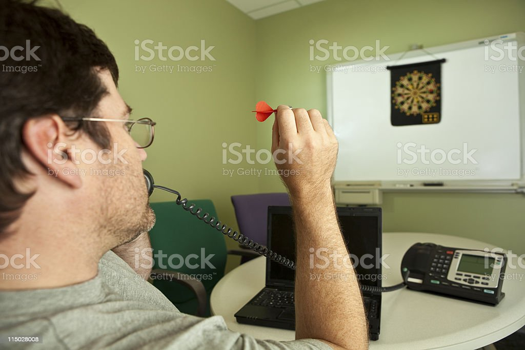 Man on phone while playing darts at work on casual Friday royalty-free stock photo