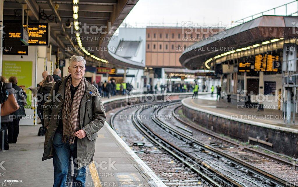 Man On Railway Station Platform Waiting For Train. stock photo