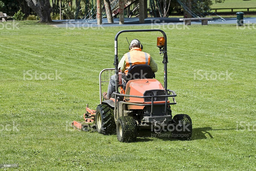 Man on Ride-On mower cutting grass stock photo