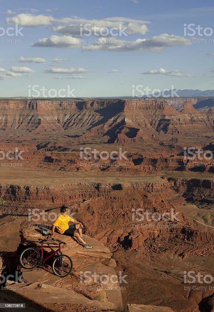 Man On Rocky Ledge Looking At View In Moab, Utah stock photo